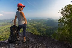 Lady hiker stands on the cliff. With backpack and smiles stock images