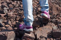 Lady hiker walking through the rocky land. Focus on the foot Royalty Free Stock Images