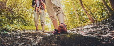 Lady hiker walking through the rocky land. Focus on the foot. Hiking shoes in action on a mountain desert trail path. Close-up of female hikers shoes stock photography
