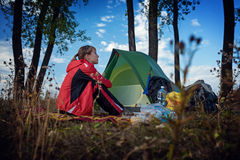 Lady hiker. Young lady sitting by the tent in the wild area royalty free stock images