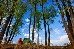 Lady hiker. Young lady sitting by the tent in the wild area royalty free stock photo