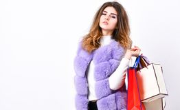 Lady hold shopping bags. Discount black friday. Shopping and gifts. Fashionista buy clothes on black friday. Girl makeup. Furry violet vest shopping white royalty free stock image