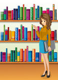 A lady holding a binder standing in front of the wooden shelves Royalty Free Stock Photography