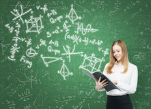 Lady is holding a black document folder and a range of math formulas are drawn on the green chalkboard. Royalty Free Stock Images