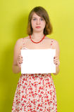 Lady holding a blank paper. On green background stock photography