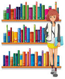 A lady holding a book standing in front of the bookshelves Stock Photo