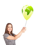 lady holding a green globe balloon Stock Photos