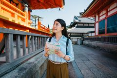 Lady holding guidebook while visiting the temple. Elegant lady holding the guidebook while visiting the famous temple in Japan. young woman sightseeing in Otowa stock images