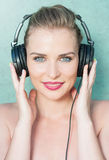 Lady holding headphones and listening to music Stock Images