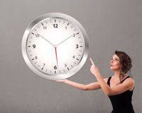 Lady holding a huge clock Royalty Free Stock Photography