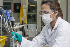 Lady holding and investigating chemicals in test glass. Image of Lady holding and investigating chemicals in test glass Royalty Free Stock Images