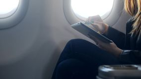 Lady holding modern tablet in hands and sitting in airplane. Profile and side view of calm and intelligent woman, who sitting near window in soft airplane seat stock video