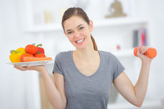 Lady holding plate vegetables in one hand and dumbbells in other Royalty Free Stock Photography