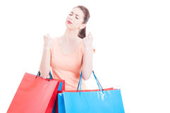 Lady holding shopping bags with eyes closed hoping or wishing Royalty Free Stock Images