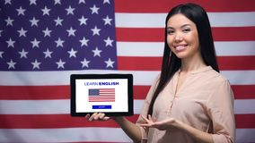 Lady holding tablet with learn English app, USA flag on background, education. Stock footage stock footage