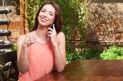 Lady holding telephone and showing thumb up outdoor Royalty Free Stock Photography