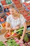 Lady holding wicker basket vegetables selecting radishes. Lady holding wicker basket of vegetables, selecting radishes Stock Image
