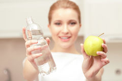 Lady holds bottle of water and apple Stock Image