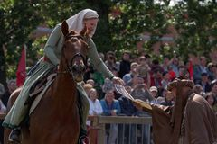 Lady on horse getting honor certificate for the contest on sword skills. St. Petersburg, Russia - July 9, 2017: Women in medieval clothes on a horse getting Stock Photo