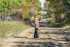 Lady hunter on dirt road with a rifle giving a thumbs up. stock images