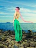 Lady i grön klänning på seashoren Fotografering för Bildbyråer
