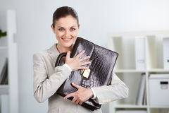 Lady with ideas. Portrait of smiling businesswoman with briefcase looking at camera in office Stock Images