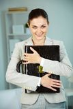 Lady with ideas. Portrait of smiling businesswoman with briefcase looking at camera in office Stock Image