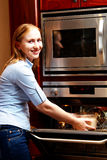 Lady infront of a open oven. Beautiful blond woman standing infront of a open oven putting a dish in side royalty free stock photos