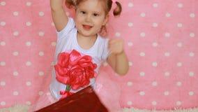 lady innegrej Den roliga gulliga lilla flickan klär upp och försöker på en röd påse arkivfilmer