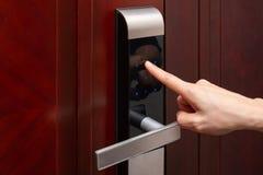 Lady inputing passwords on electronic door lock. Lady inputing passwords on an electronic door lock royalty free stock photos