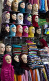 A lady inspects the variety of colourful headscarves for sale in the Fez medina, Morocco. royalty free stock image