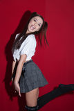 Lady in Japanese anime cloth style. Cute lady in Japanese anime cloth style wearing white tied shirt, skirts and knee socks on red background, standing in stock photography