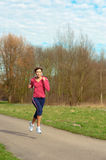 Lady Jogging in a Park. Young beautiful lady jogging in a park stock photos