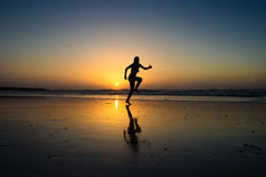 Lady jumping on a seashore. With sunset on the back Royalty Free Stock Photos
