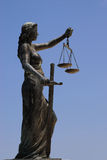 Lady Justice. Side view of female statue with sword and scales of justice, blue sky background Stock Images