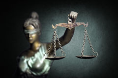 Lady Justice on emerald background. Lady Justice is an allegorical personification of the moral force in judicial systems . Her attributes are a blindfold, a stock photography
