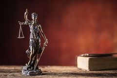 Lady Justicia holding sword and scale bronze figurine with book. On wooden table stock images