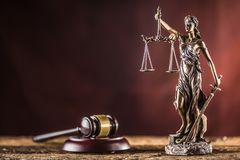 Lady Justicia holding sword and scale bronze figurine with judge. Hammer on wooden table stock photography
