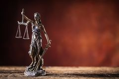 Lady Justicia holding sword and scale bronze figurine on wooden. Table stock photos