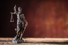 Lady Justicia holding sword and scale bronze figurine on wooden. Table stock photography