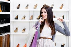 Lady keeps credit card in footwear shop Royalty Free Stock Photos