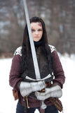Lady knight. Beautiful young woman in medieval clothes holding a sword Stock Photo