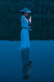 Lady of the lake. Young woman in a white dress with candelabrum standing in still water of the lake at dusk Stock Photos