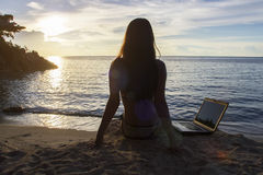 Lady with a laptop on the beach. On the sunset Stock Photos