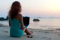 Lady with a laptop on the beach Stock Photo