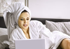 Lady with laptop on bed Stock Photo