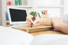Lady with laptop writing in notepad. Close up of lady`s hands writing in spiral notepad placed on wooden desktop with blank laptop screen. Paperwork concept royalty free stock images