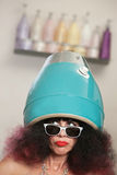 Lady in Large Hair Dryer. Serious lady looking over with head in hair dryer royalty free stock image