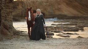 Lady leads a horse at sunset along the seashore in a historic costume of the 19th century stock video