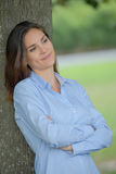 Lady leaning against tree Stock Photography